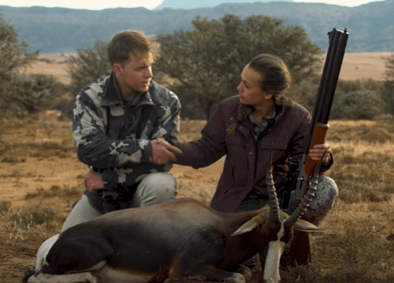 Mattie shakes the hand of the Bontebok she just hunted. her cameraman in front of