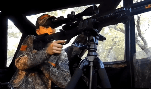 Man looks through scope of a gun that is sitting on a tripod