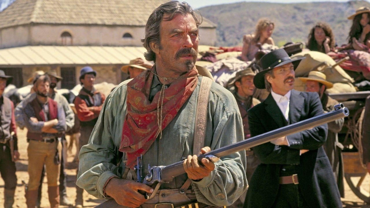 Quiqley is wearing western clothes while holding a gun and looking into the distance.
